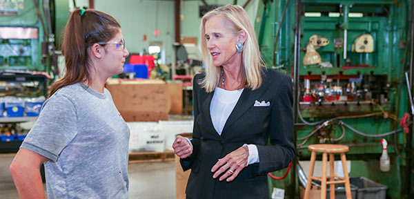 Senator Hartley on a factory floor.